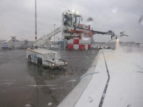 Pemadangan dari dalam pesawat KLM Fokker 70 ketika proses de-icing tengah berlangsung