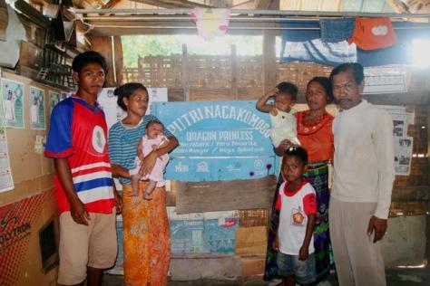 Pak Ishaka Mansyur dan keluarga dengan latar papan nama yang menjadi kebanggaannya