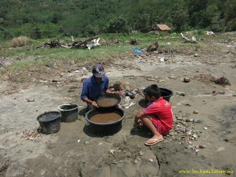 Pak Heri dan anaknya tengah mendulang emas dari kumpulan pasir yang sudah disaring