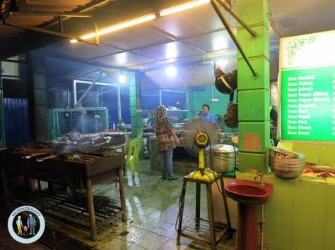 """Dapur yang mengepul menyebarkan bau ikan bakar yang menggoda selera di """"Ana Ikan Bakar Petai"""", Kuantan, Pahang"""