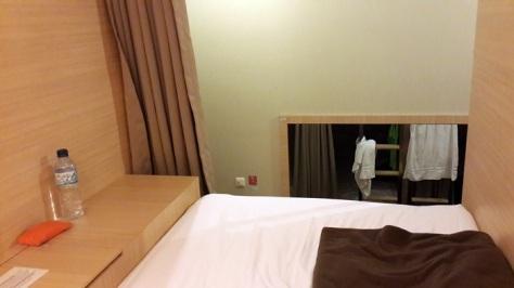 Foto dari dalam ranjang saya, sebelah kiri ada lemari kecil yang bisa dikunci, sementara kanan kirinya berupa dinding kayu, dan depannya berupa tirai yang bisa ditutup