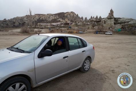 Mobil sewaan kami di Cappadocia, Turki, dengan latar satu kampung yang berisi rumah-rumah dari batu yang dipahat