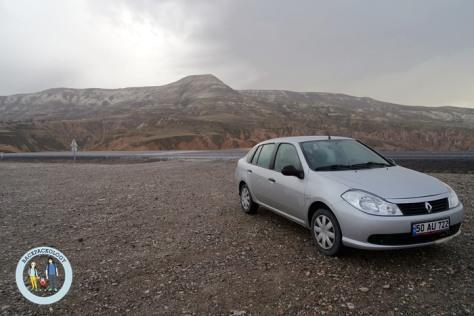 Mobil sedan Renault, pilihan termurah kali ini, dengan latar pegunungan Cappadocia yang mistis