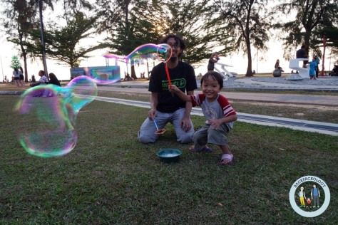 Anak-anak pasti senang bermain gelembung busa di Pantai Morib, tak terkecuali si Oliq yang sangat ceria